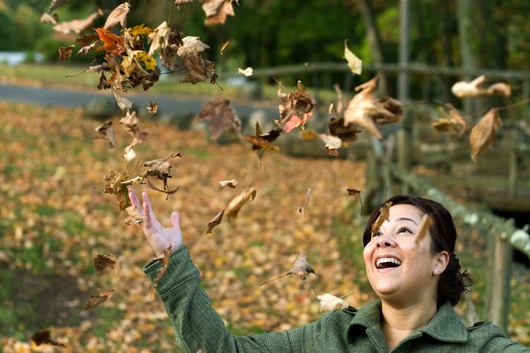 Woman Laughing As The Leaves Fall All Around Her During The Autumn Season