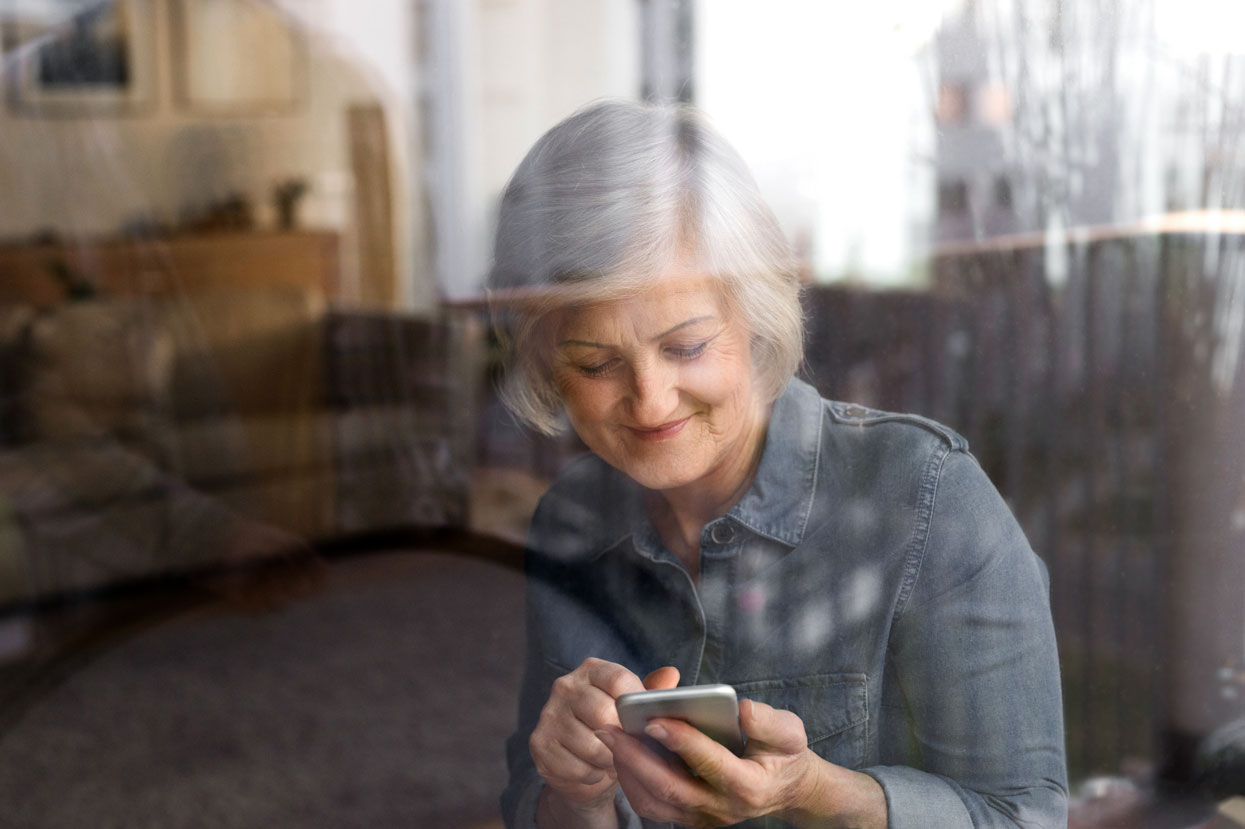 Elderly woman typing into mobile phone
